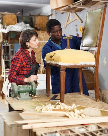 Portrait of male and female restorers working with vintage wooden armchair in workshop