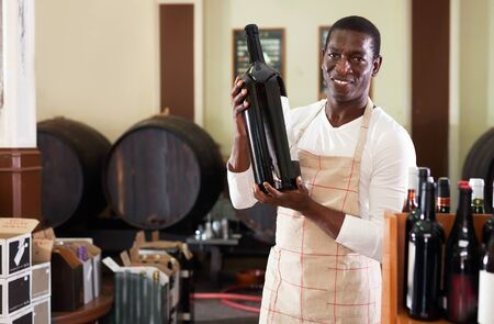 Smiling diligent cheerful  salesman in apron proposing wine in bottles in winery shop