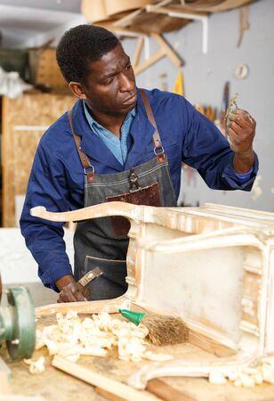 Portrait of furniture restorer in process of renewing vintage bureau at workshop
