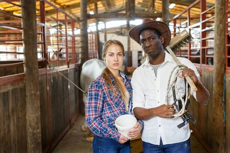 Happy afro man and European girl in working clothes posing at horse stable