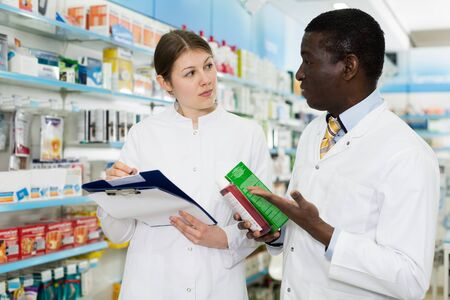Two confident positive pharmacists working at drugstore, checking medicines inventory