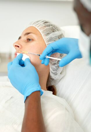 Man doctor in mask making beauty injection to female client in estetic clinic Reklamní fotografie