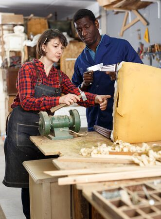 Woman and man carpenters inspecting old wooden chair in studio 写真素材