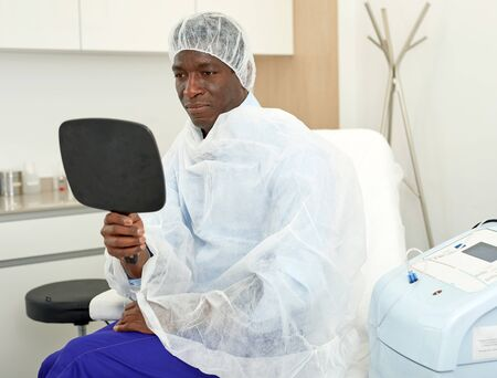 Man sitting in armchair and looking to mirror after procedure in clinic of esthetic cosmetology Reklamní fotografie