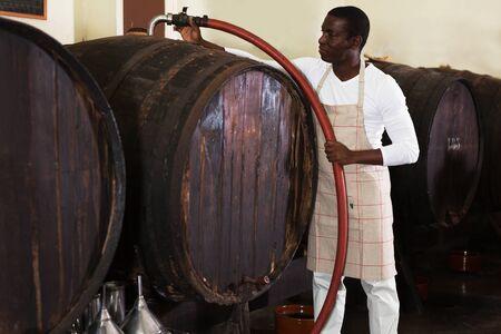 Confident man winemaker working in wine-vault, filtering wine in barrels