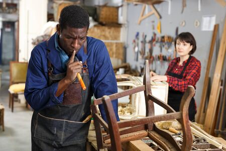 Portrait of furniture restorer in process of renewing vintage chair at workshop