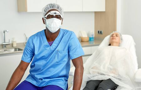 Cosmetician male in mask  before aesthetic facial injection, woman in amchair in medical  office