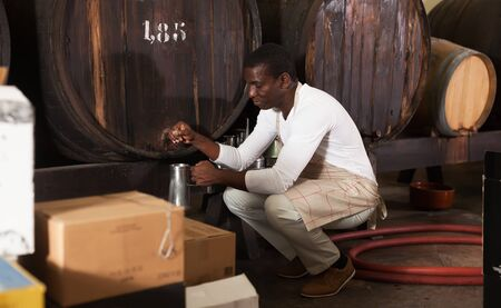 Confident man sommelier pouring wine to mug for tasting Stok Fotoğraf