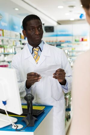 Confident man pharmacist working in pharmacy, counseling customer about prescribed medication