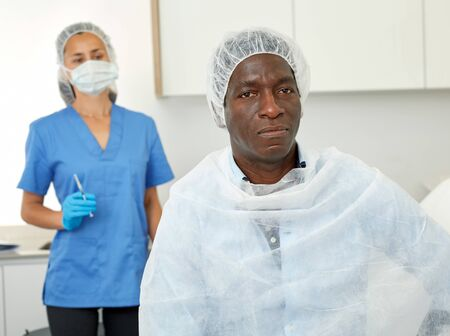 Sad man sitting in armchair before beauty procedure in clinic of esthetic cosmetology, woman on background
