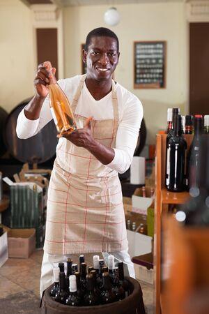 Smiling glad salesman in apron proposing wine in bottles in winery shop Stok Fotoğraf