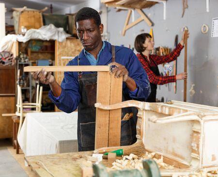 Woman and man carpenters using tools for restoration wooden bureau in studio 写真素材