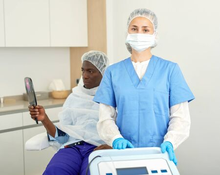 Cosmetician female in mask standing before aesthetic facial injection, man with mirror in medical  office