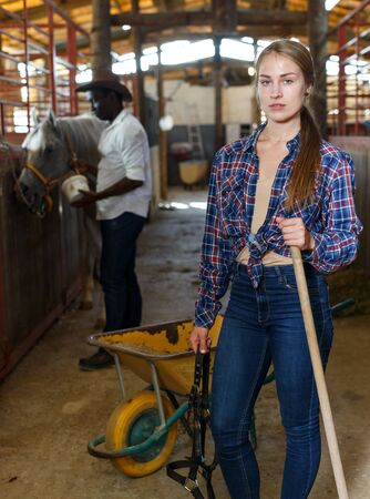 Portrait of young woman horse farm worker standing at stable