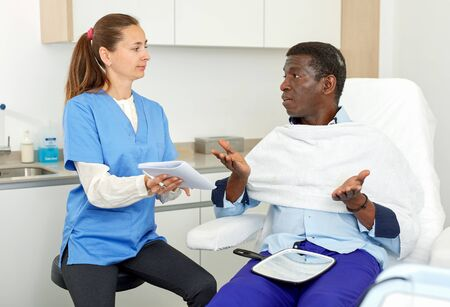 Cosmetician female with papers talking to man before procedure in medical esthetic office Reklamní fotografie