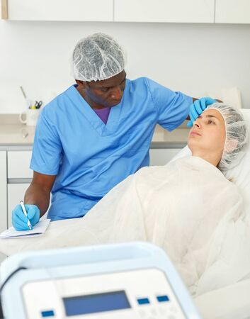 Cosmetician male examining patient face skin before aesthetic procedure and writing to workbook in medical  office