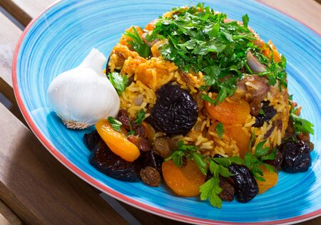 Tasty piquant pilaf from lamb, prunes, dried apricots, raisins with oriental spices, garlic and greens