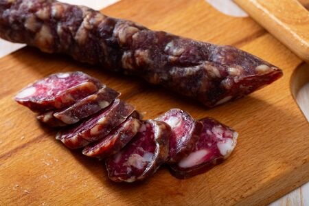 Traditional French thin dry cured sausage sliced on wooden surface
