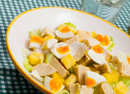Tasty salad with chicken,  egg and sweet pineapple at plate Stock Photo