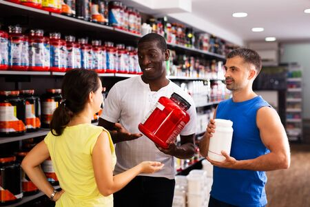 Group of interested athletic people holding plastic jars with sports nutrition discussing in shop interior