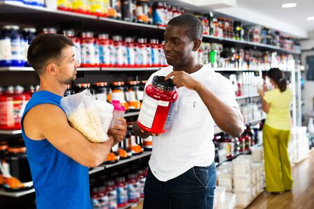 Adult muscular man choosing sports supplements in store, consulting polite African seller