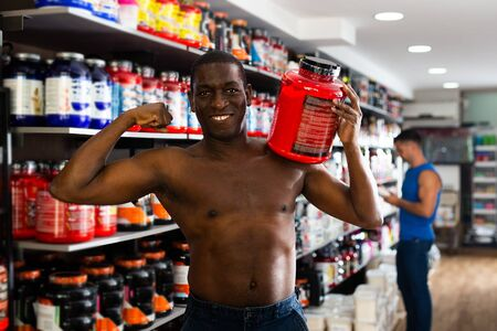 Nice athletic shirtless African man with jars of sports nutritional supplements showing muscular body in shop interior Stock fotó