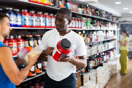 Adult serious muscular man choosing sports supplements in store, consulting polite positive African seller