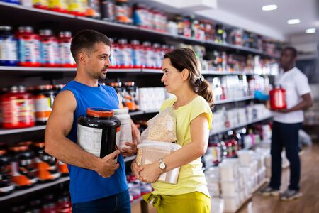 Ordinary athletic man and smiling woman holding plastic jars with sports nutrition talking about food supplements in store Stock fotó