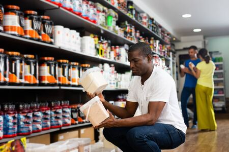 Interested athletically built African purchaser looking for sports nutrition, reading label carefully before buying in shop
