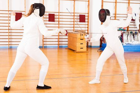 active young female athletes in uniform practicing  movements at fencing battle