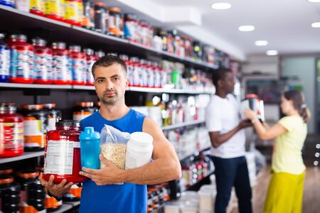 Young muscular man with jars of sports nutritional supplements in store