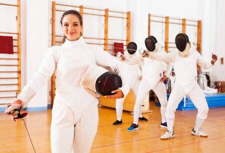 happy sporty female in uniform standing at fencing room