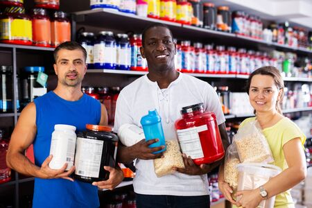 Portrait of interracial group of sporty adult people standing in store, holding cans of sport nutrition Stock fotó