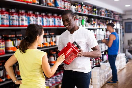 Confident athletically built African man recommending sports supplements to female client at sports nutrition store