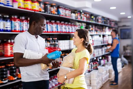 Woman and her African friend discussing modern food supplements in sports nutrition store