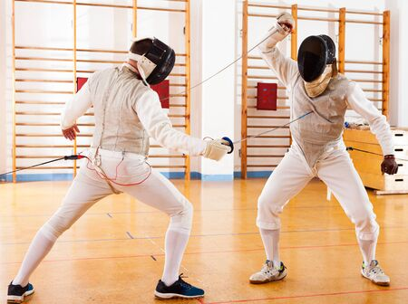 active fencers at fencing workout, practicing attack movements in battle