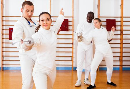 Glad cheerful positive smiling woman fencer practicing new movements with trainer  at fencing room