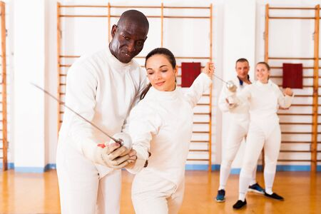 Female fencer practicing  movements with african american male trainer at workout