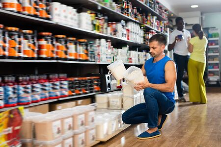 Athletic man reading label carefully before buying in shop
