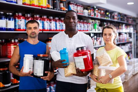 Portrait of interracial group of athletic adult people standing in shop, holding cans of sport nutrition Stok Fotoğraf