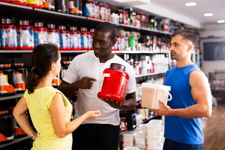 Group of athletic people holding plastic jars with sports nutrition discussing in shop interior