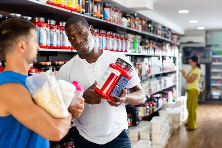 Confident cheerful positive African seller offering diet and sports supplements to interested athletic person in sports nutrition store