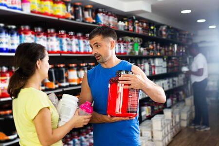 Young interested woman choosing diet and sports supplements in store, consulting competent seller