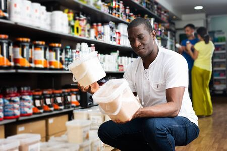 Athletic African looking for necessary food supplements in sport nutrition store