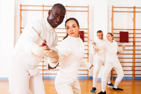 portrait of female fencer practicing  movements with african american male trainer at workout