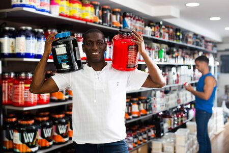 Satisfied athletic African standing in store, holding big cans of sport nutrition