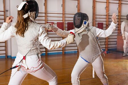 Portrait of female athletes practicing movements at a fencing workout 스톡 콘텐츠 - 132123591