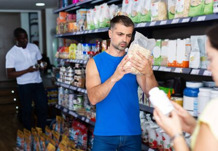 Portrait of interested sports man choosing food supplements in large assortment of sport nutrition store