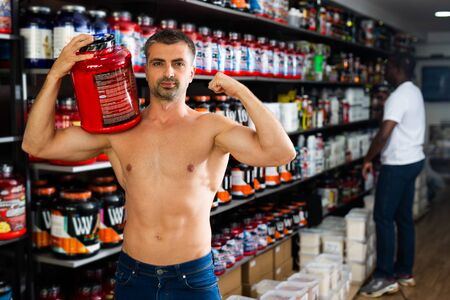 Bare-chested athletic man standing with cans of sports nutrition in store, demonstrating muscles