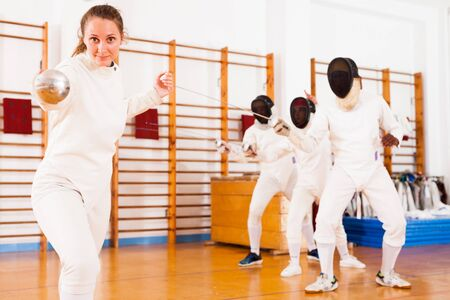 Sporty young female fencer practicing fencing technique in training room